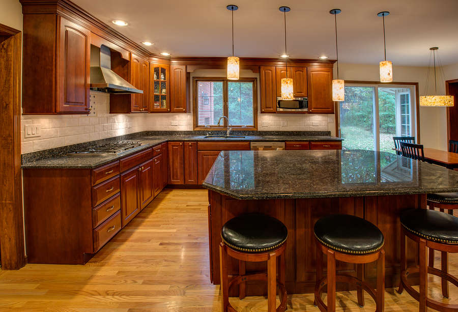 Corner Newly Finished Kitchen With Granite Counter Top Hardwood Cabinet And Floor Stainless Steel Fridge